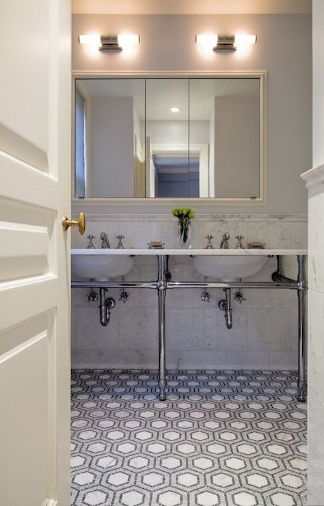 A cream paneled door opens to bathroom boasting gray paint on upper walls and marble tiled wainscoting on lower walls lined with a 3 leg washstand topped with marble farming his and her sinks and vintage style faucets under a cream beveled vanity mirror illuminated by side by side sconces over a white and gray marble hex floor.
