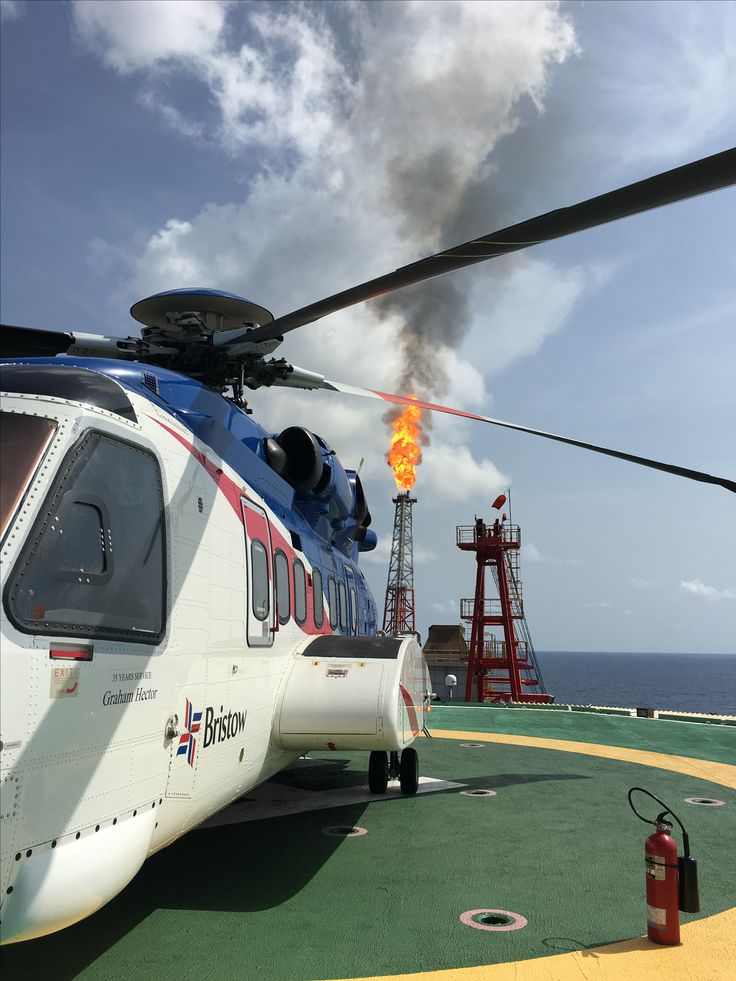 Sikorsky 92 on the deck of the AGBAMI FPSO with the flare in the background.