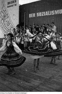 Dresden, Veranstaltungen zum 10. Jahrestag der DDR, Staatsfahne mit 3 Arbeitern des VEB Otto-Buchwitz-Werk Dresden, Umzug in der Innenstadt, u.a., 1959