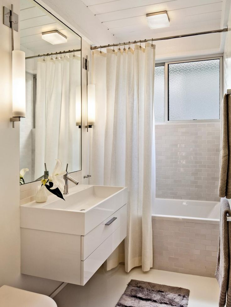 An all-white color palette keeps this small bathroom feeling more open and spacious. A floating sink and simple sconce lighting give the space a sleek, clean feel.