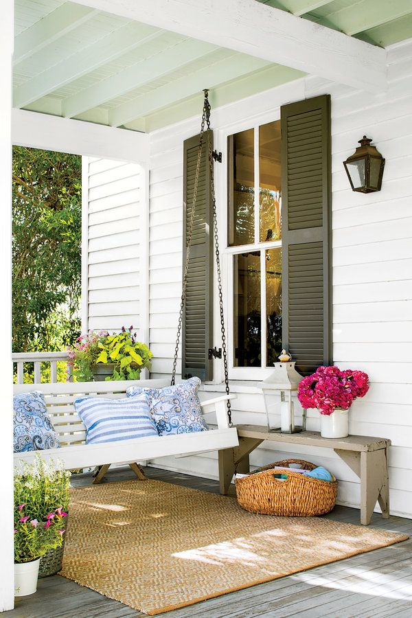 A traditional wooden porch swing is cozied up with blue-and-white cotton pillows from HomeGoods. A rustic bench serves as a side table.