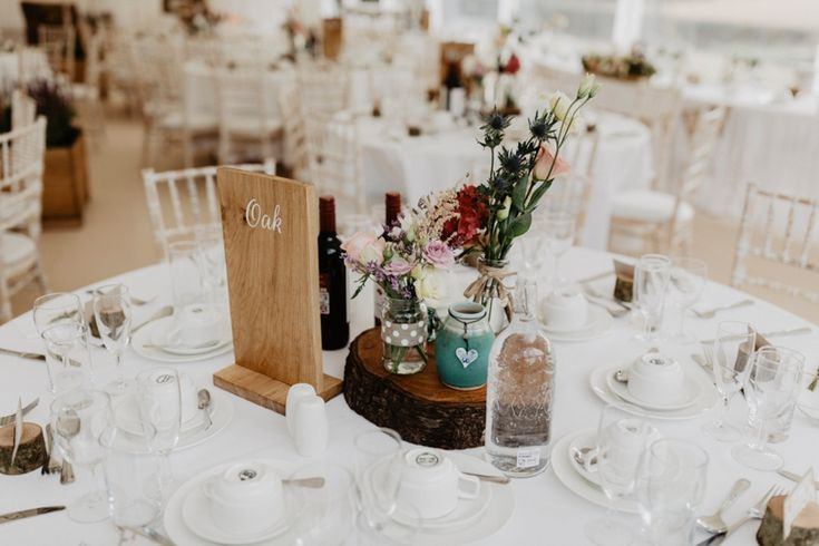 The wood theme continues with tree stump table centres, wooden table name placards and lovely flowers in a variety of glassware. Photo by Benjamin Stuart Photography #weddingphotography #weddingdecor #receptiondecor #marqueewedding #diywedding #tablecentres #woodtheme