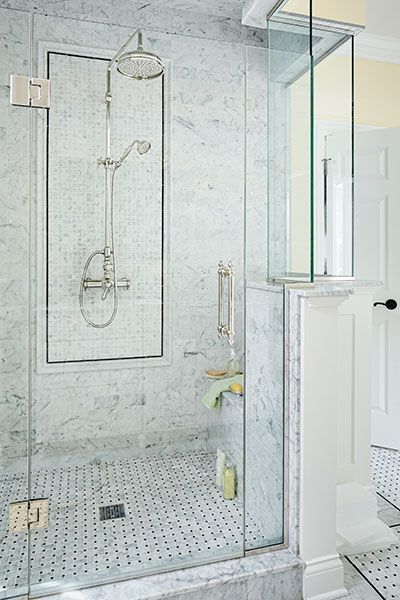 A clear glass enclosure keeps sight lines open in this master bath shower which is lined with marble tile and a matching basketweave floor. A built-in bench offers a resting spot for toiletries.
