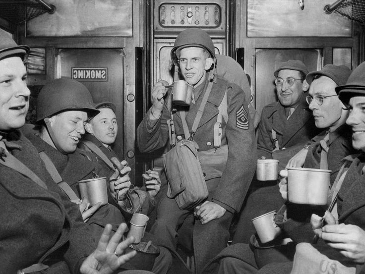 This group of US soldiers who debarked from a transport drink from mugs of coffee and munch doughnuts on a troop train en route to their station in England, March 15, 1944. From left: Sgt. J.A. Michalski, Detroit, MI; Sgt. Roger E. Sebring, Scranton, PA.; Sgt. O.C. Parson, Cleveland, OH; Sgt. Jack Ehmke, Angola, NY,; Sgt. P. Kreitszberg, NY; Sgt. Leonard Catton, Union City, NJ; and Sgt. Walter R. Van Liuit, Cleveland, OH. AP photo, via TheAtlantic.com
