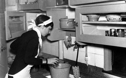 Keukeninrichting 1934. Dienstbode bij de gootsteen bezig met een emaille emmer. Granieten aanrecht, emaille pan.