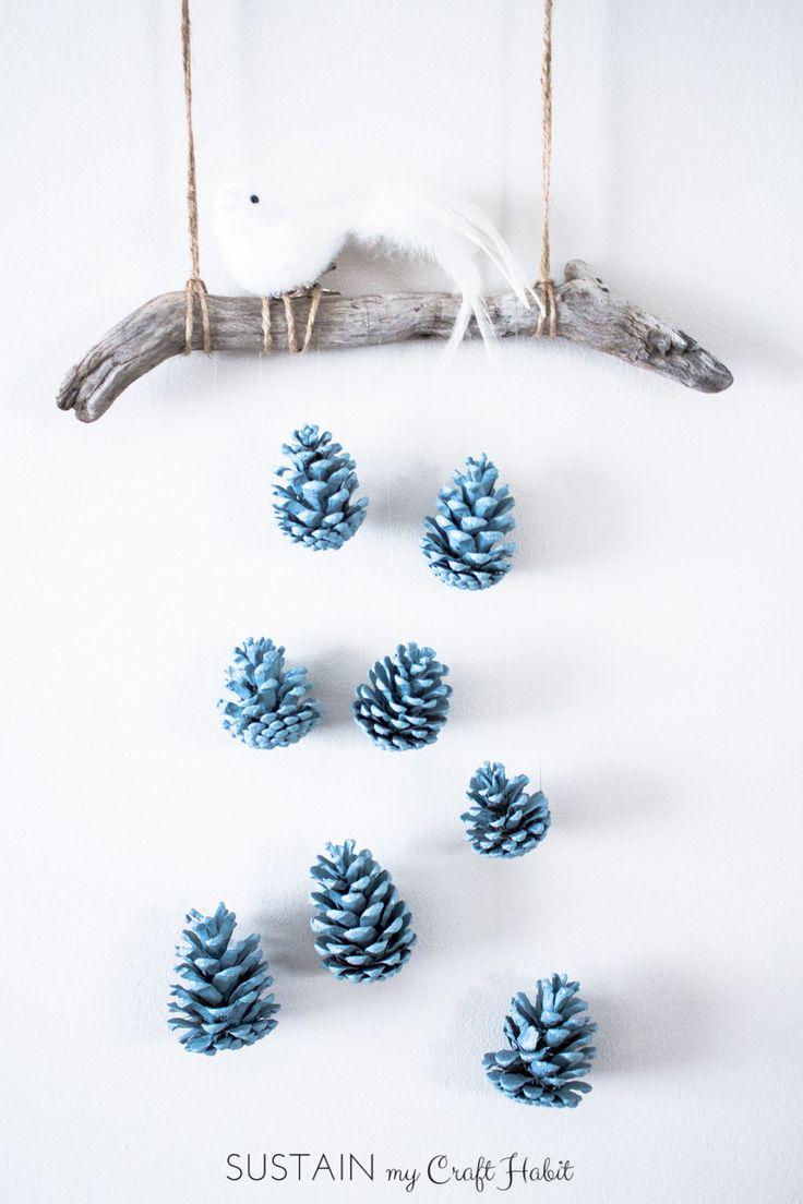 Um pássaro bonito empoleirou-se acima de uma disposição de conexão em cascata dos pinecones azuis do ovo do pisco de peito vermelho faz uma idéia rústica bonita, barata e fácil da arte da parede de DIY.  Confira o tutorial detalhado passo-a-passo.