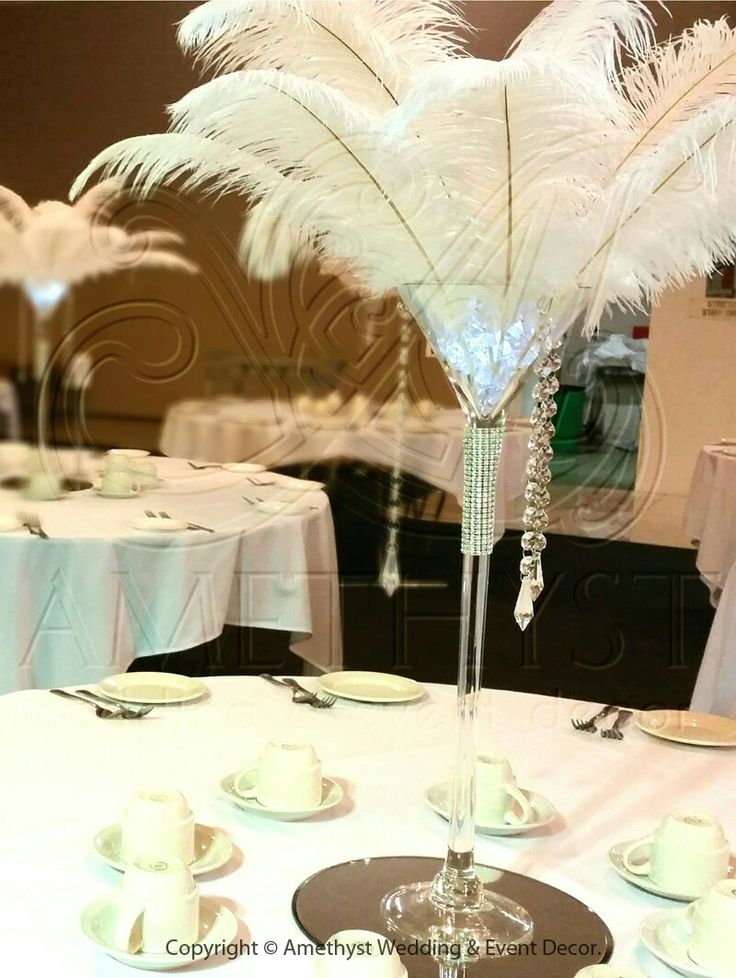 Great Gatsby martini glass centerpiece with ostrich plumes, crystals, gel beads, and submersible LED. I would add orchid stocks in between the plumes. Great centerpiece for a very fun wedding!