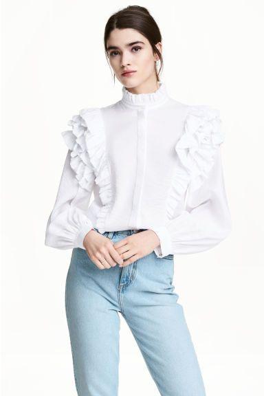 Bluzka z falbanami: Bluzka z cienkiej tkaniny z krytym zapięciem z przodu. Stójka z falbankowym brzegiem, falbany na ramionach. Długie, szerokie rękawy z mankietem.