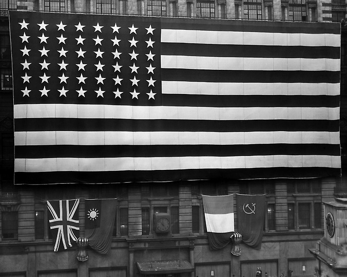Caption from Pinterest, World War Items: A huge American flag unfurled in New York's Herald Square on VE Day on May 8, 1945. This 80x160 foot flag was hung from the eighth floor balcony of Macy's New York department store, covering the façade from 34th and 35th Streets along Broadway. Beneath it were placed a set of British, Chinese, French and Russian flags, held by two giant mailer fists. (AP Photo)