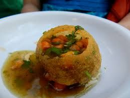 "Pani Puri is a popular street snack in India, Pakistan, Bangladesh, and Nepal. It consists of a round, hollow puri, fried crisp and filled with a mixture of flavored water (""pani""), tamarind chutney, chili, chaat masala, potato, onion and chickpeas. It is generally small enough to fit completely into one's mouth."