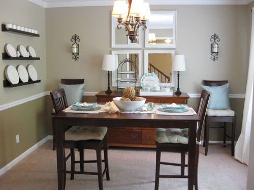 I like a nice, classic look with modern twists. Great neutrals here with blue pops of color. Chair rail, dark wood, layered neutral, blue pop, mirror wall, chandelier, display shelving, dining room