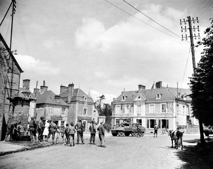Un groupe de soldats américains dont 4 MP à la fontaine du village entourés par femmes et enfants,le 12 juin à Sainte-Marie-du-Mont. Le GI à gauche nettoie ses gamelles. Le même groupe sur 3 photos : p011591, p011592 et p011594. Sur les façades des bâtiments : BOURRELLERIE, BOUCHERIE  E. DESMONTS, l'étage et la fenêtre de toit ont été mitraillés. Le bâtiment derrière le blindé M 8 : Ste MARIE du MONT  PTT CAISSE NATIONALE d'ÉPARGNE Un GI est assis sur le Monument aux morts, voir ici: ...