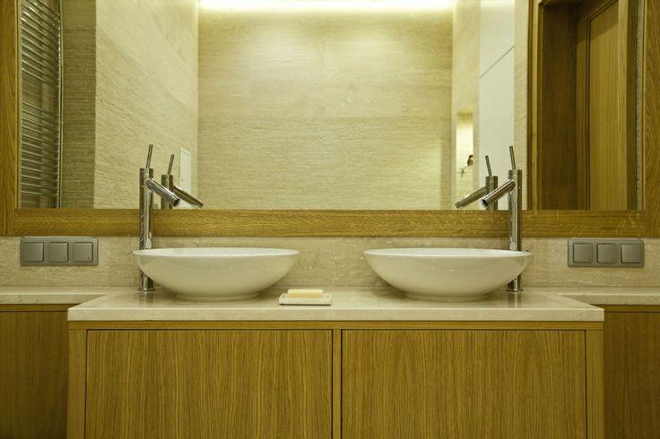 Zabudowa łazienki w piaskowym kolorze ma pojemne schowki, które kryją drobne kosmetyki, a także pralkę. Na uwagę zasługują ciekawe podświetlenia wnęk, dzięki którym w łazience mamy przyjemną i nastrojową elegancję. Podpowiadamy, jak ukryć pralkę w łazience.