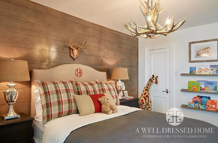 Country cabin boy's room features a faux antler chandelier hanging over a tan camelback ...