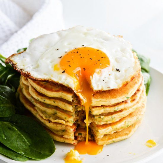 Savory pancakes made with sour cream, sun-dried tomatoes and parsley; topped with a crispy fried egg and spinach with lemon.