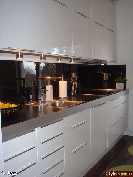 """Vitt och svart kök, med för närvarande limegrön accentfärg. IKEAs högblanka Abstrakt-luckor och svart glasskiva som stänkskydd. Köket är inte riktigt färdigt ännu (trots att vi renoverade det 2007...), fattas en vin- och glashylla som ska vara mellan högskåp och vägg mittemot """"kokbokshyllan"""". Har..."""