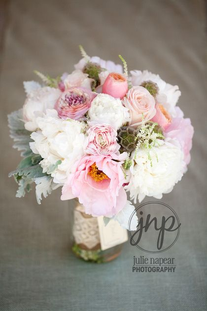 Blush bridal bouquet by Sachi Rose. Includes tree peonies, peach garden rose, grey dusty miller, variegated ranunculus, scabiosa pods and astilbe wrapped in burlap in vintage lace.