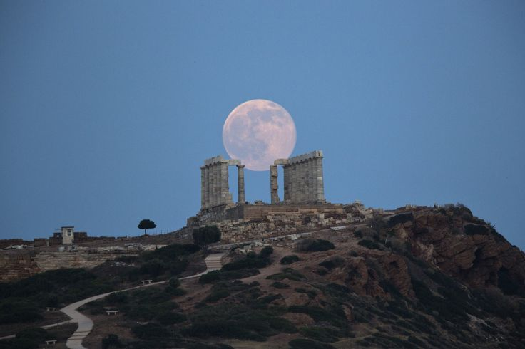 """20aliens: """" The full moon rises behind the columns of the ancient marble Temple of Poseidon at Cape Sounion, southeast of Athens, on the eve of the summer solstice on June 20, 2016. The temple located on a promontory at Cape Sounion, about 70km (45..."""