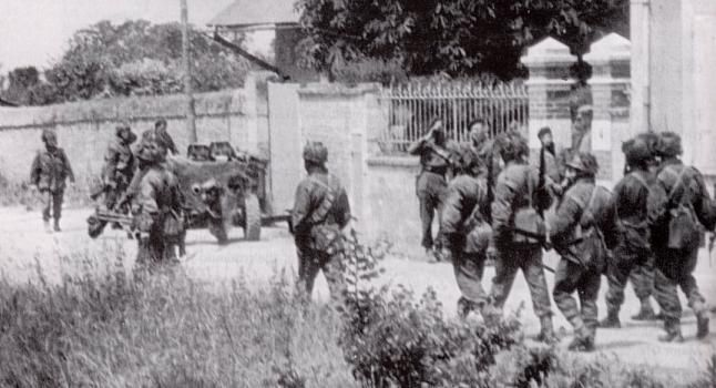 Commandos (wearing berets) and 9th Battalion men (in helmets and bulky Denison smocks) in Amfreville.
