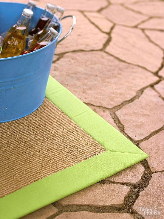 An area rug pulls together the elementsof an outdoor room. This rug includes a green border that complements the Adirondack chairs and umbrella. Our favorite feature: It can simply be hosed off when it gets dirty./