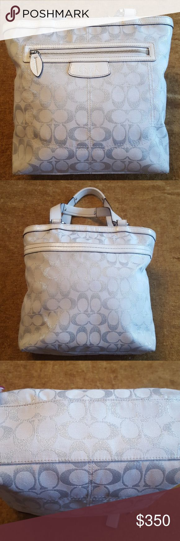 NWT COACH EMBELLISHED SILVER COACH LARGE HANDBAG NWT COACH HANDBAG, COLORS ARE OFF-WHITE  BASE COLOR WITH EMBELLISHMENTS OF THE COACH LOGO IN SHINY SILVER THREADING TO MAKE IT SPARKLE☄. IT HAS LAVENDER SATIN INSIDE LINING WITH A DEEP ZIPPER POCKET & 2 OTHER POCKETS. ON THE OUTSIDE IT HAS A LARGE DEEP POCKET IN THE BACK & A DEEP ZIPPER POCKET ON THE FRONT BY THE LOGO. ALL THE ACCENTS ARE SILVER OR LEATHER. DIMENSIONS ARE 16×14×4. CAN CARRY TONS OF THINGS IN THIS MY DEAR. I BOUGHT IT IN NEW…