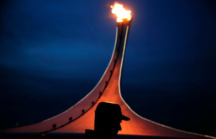 A visitor to Olympic Park is silhouetted while walking past the Olympic cauldron at the 2014 Winter Olympics, Thursday, Feb. 20, 2014, in Sochi, Russia. (Photo by David Goldman)
