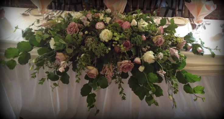Long and Low top table arrangement of Hazel Leaves, Roses, Lisianthus and Ammi.