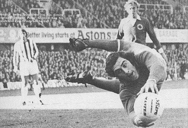 28th October 1972. Leicester City goalkeeper Peter Shilton diving to save watched on by Stoke City striker Geoff Hurst and team mate Graham Cross, at the Victoria Ground.