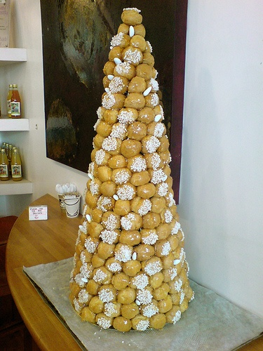 Croquembouche. Traditionally the Croquembouche used to be hit by a sword, silver mallet or a champagne, which used to crack its upper portion and the bridesmaids collected them by holding the corners of tablecloth