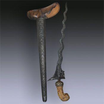 "Keris Naga Kikik - Jogyakarta  17th century 13 ""Luk"" Keris dapur Naga Kikik tangguh Mataram Sultan Agung (1613 to 1646), warangka gayaman Jogyakarta, central Java, hilt carved in an elephant ivory, sheath made from Timoho wood.  The base of the blade represente a dog, similar in shape to the ""Singa Barong"" which represente a lion. The pamor is ""Wos Wutah""."