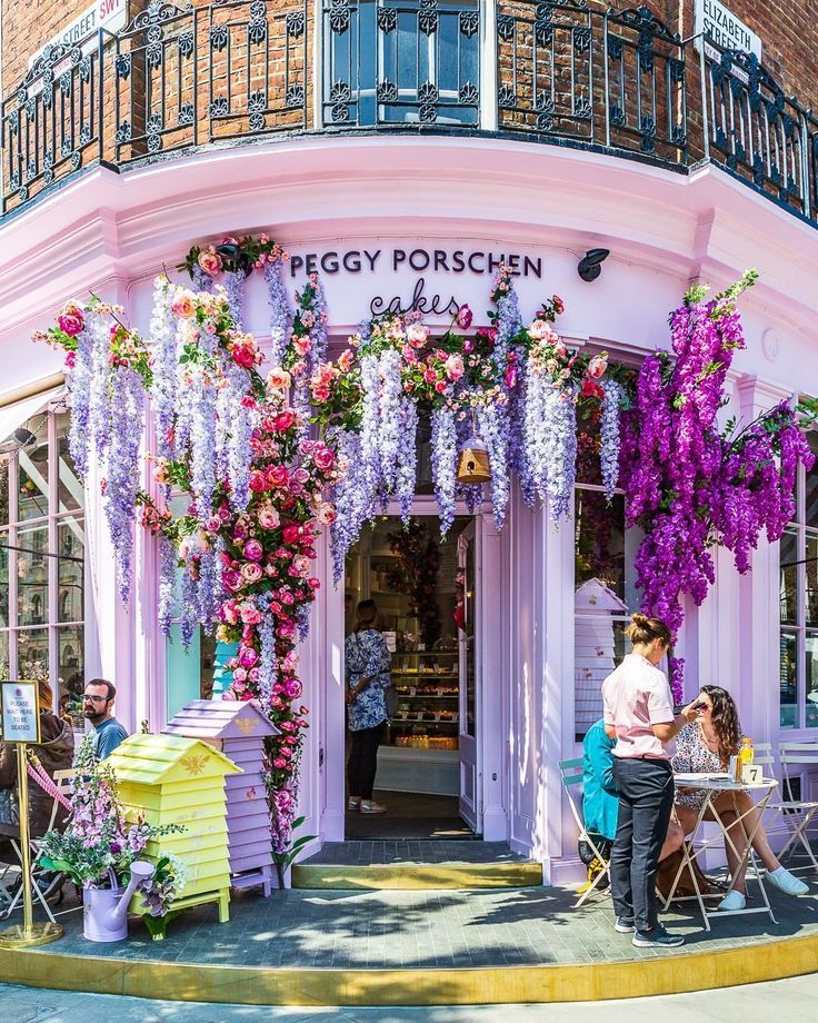 Flowers adorn the facade of a pretty pink cake shop in