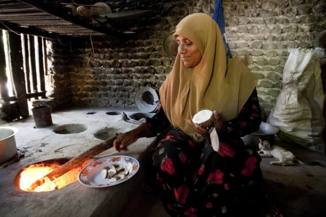 Woman cooking in kitchen of her village home, Northern Islands, Maldives. - Felix Hug/Getty Images
