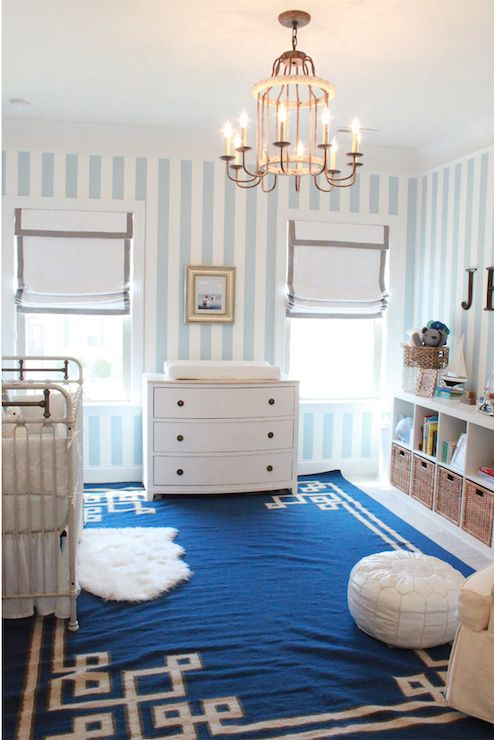 White and blue boy's nursery features blue and white striped wallpaper framing windows dressed in white roman shades with gray grosgrain trim