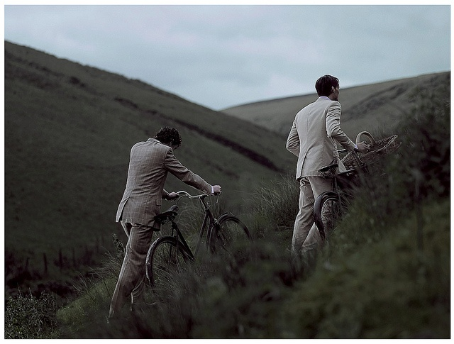 Now I'm not sure why you'd be wearing a nicely tailored suit and walking your bike up a large hill, but I can only imagine they're meeting their ladies for some kind of fantastic picnic.