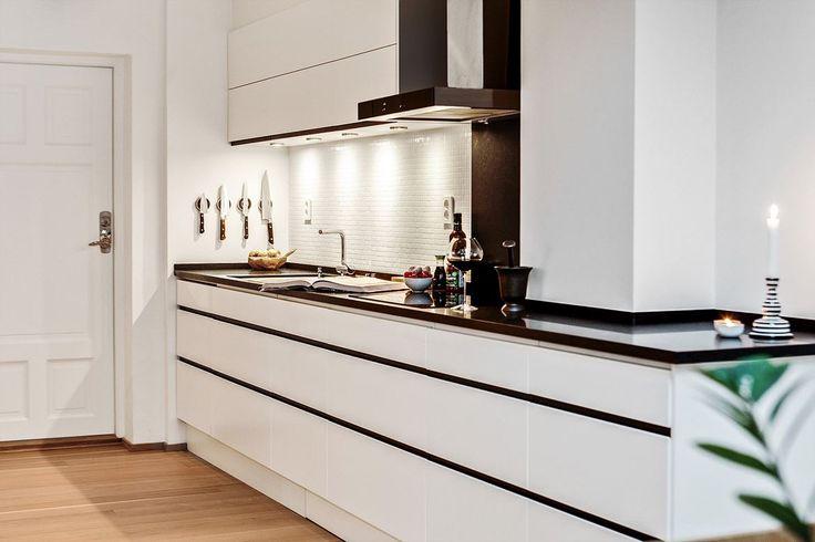 Snyggt och stilfullt kök, med inredning i klassiskt svart och vitt. De vita luckorna kommer från gedigna Ballingslöv och samtliga vitvaror är av högsta kvalitet. Bänkskivorna är av svart granit och väggen pryds av dekorativ vit glasmosaik.