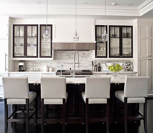 Ideas for Kitchen! (Jennifer Worts Design.    Gorgeous kitchen design with white kitchen cabinets, marble tiles backsplash, glass pendants, espresso kitchen island, espresso upper doors inside whit cabinet, marble counter tops, chrome faucet and hardware and white leather stools.)