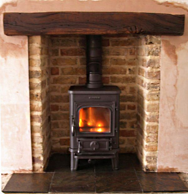 Reclaimed brick slip chamber with slate tiled hearth, clad oak beam and Morso Squirrel 1430 multifuel stove. Fitted in rochford Essex 2002