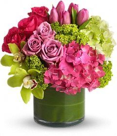 Vase arrangement of pink and green hydrangea, pink tulips, lavender roses, and hot pink roses, green cymbidium orchids in a ti leaf wrapped clear glass cylinder vase