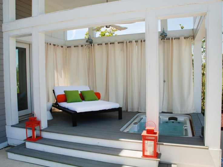 Curtain panels add privacy and protection from the elements in this transitional outdoor space. Safe from prying eyes, guests can curl up on the luxurious daybed or soak in the sunken tub nestled into the wood deck.