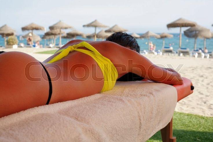 Massage area on the beach with suntanned beautiful woman lying down on summer vacation season   Stock Photo   Colourbox on Colourbox