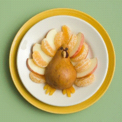 Gobble me up!  1  Arrange apple and clementine or navel orange slices on a plate as shown, and lay a cored pear half on top.    2  Use scissors to halve a dried apricot, then snip small triangles from each half and tuck them under the pear to form the feet.    3  Finally, use peanut butter or softened cream cheese to attach mini chocolate chip eyes, a nut beak, and a dried cranberry snood.