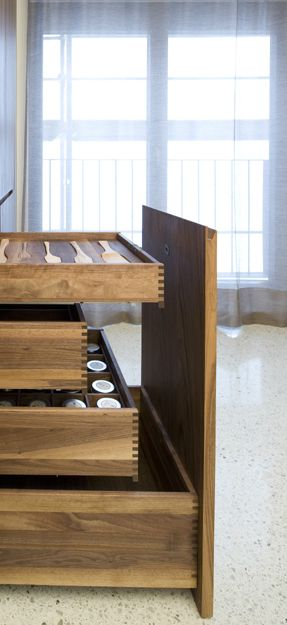 Large, extractable panel hidding multiple drawers inside this custom made kitchen by Holzrausch.