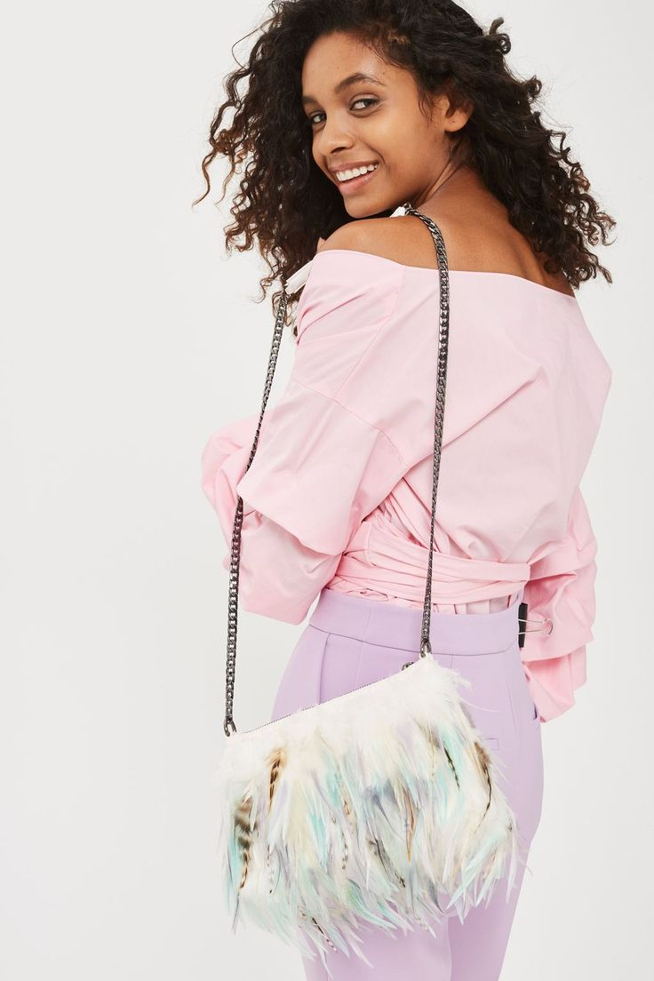 Look to feathers this season when updating your accessories collection. Layered in pretty multi coloured feathers, this striking cross body bag features a chain strap and zip top.