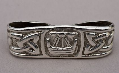 A rare Iona silver scarf ring, in the Celtic Arts and Crafts style. The ring is very good quality, and has a classic Ritchie Viking longship motif, with celtic knotwork side panels, and terminals of wolf like celtic beasts. The ship is copied off an 11th century stone carving in Iona's Abbey museum, and the beasts are similar to those found in the Book of Kells. Alex Ritchie's work was inspired by the ancient Celtic and Viking carvings on Iona. circa 1934