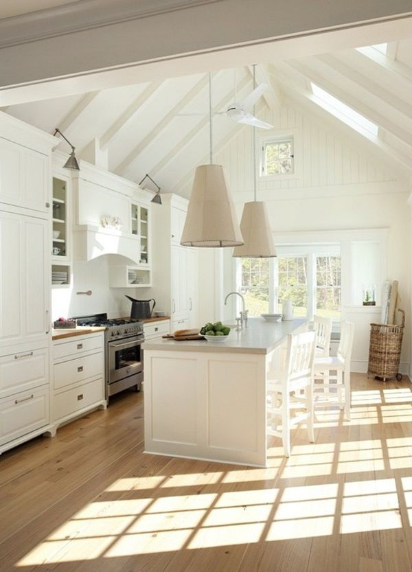 Light-soaked kitchen with cathedral ceilings, skylights, and glass doors to the outside. Custom Belgian linen pendants, Shaw's Original Farmhouse sink.