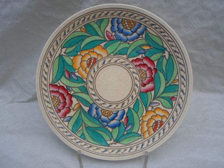 A 1930s Crown Ducal wall plaque, designed by Charlotte Rhead in the 4040 Persian Rose pattern, having a tube-lined decoration of stylised flowers with cross-hatch centres in polychrome enamels, and green leaves. This unusual variation has an unpainted border and well, the marks verso include the text 'L. Delford, Christmas 1940', so it was possibly a specially commissioned piece, printed and tubed marks verso to include a Rhead facsimile signature, 32cm diameter