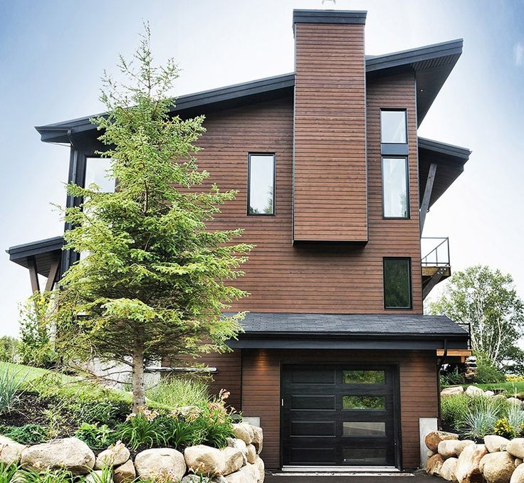 """This residential project offers a modern-looking exterior siding mostly made of genuine wood, whose """"Fundy Bay Brown"""" and """"Mystery Black"""" colours highlight the natural character of the property. The modern, board and batten sidings follow the same duo-shade tints which perfectly fits the contemporary architecture. The wide windows punctuate the design chosen for this country house."""
