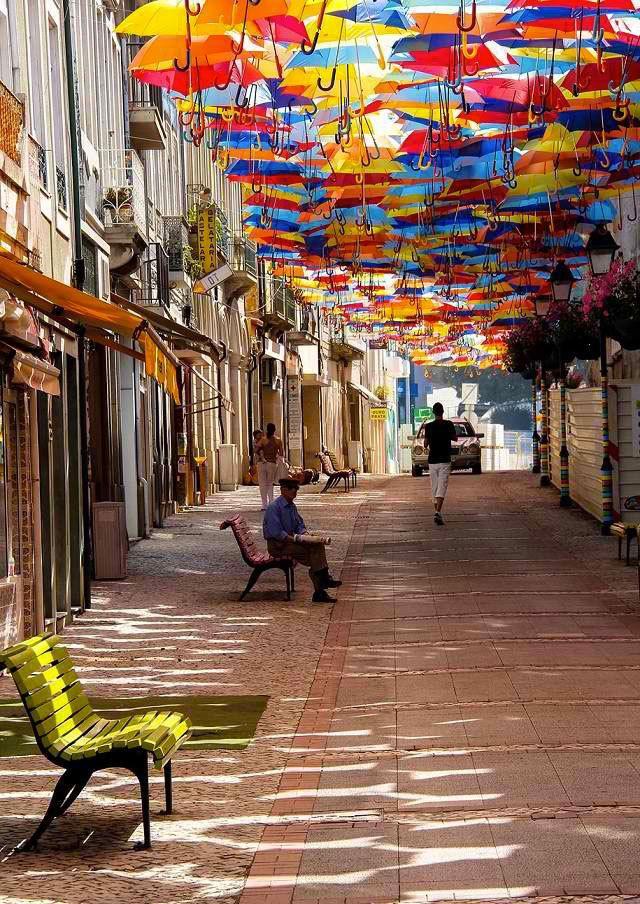 Portugal : les parapluies multicolores d'Águeda, je ne m'en lasse pas! | par Sabrina P. Foucaud, Détours du monde 18.07.2013 | Águeda, petite ville tranquille de moins de 50 000 habitants, au nord du Portugal, reconduit cette initiative originale et pleine de poésie. Une installation composée de parapluies multicolores suspendus au ciel dans les rues commerçantes de la ville pour rafraîchir les badauds durant les mois d'été.
