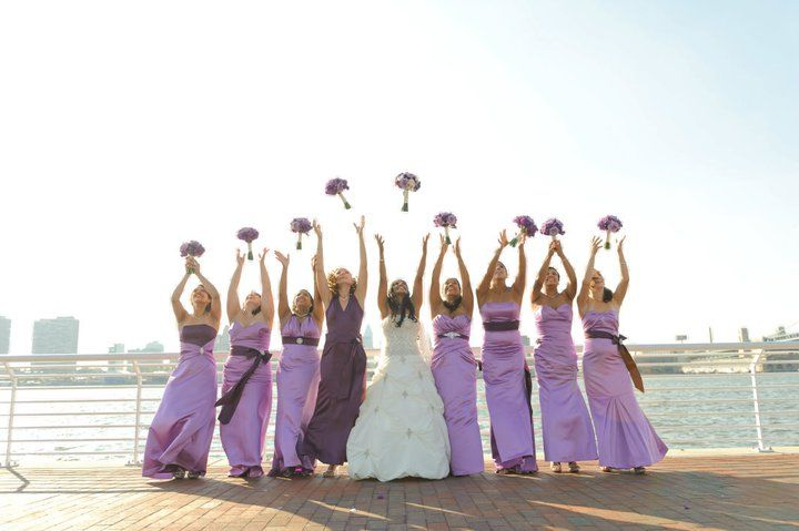 bridesmaids wearing purple dresses throwing bouquets
