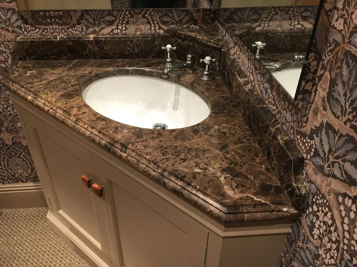 Maron Imperial marble vanity top set in a corner with small shelf to rear. shaped upstands. Waterfall edge